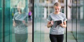Junge Frau mit Tablet vor Glasfassade